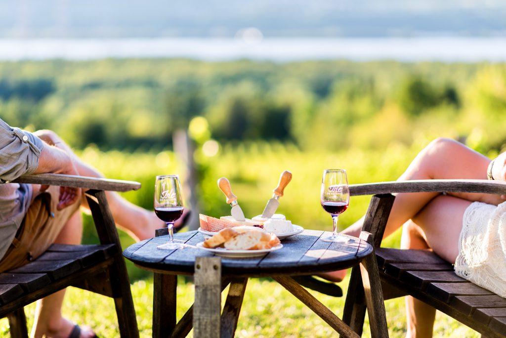 Couple admirant la vue du St-Laurent autour d'un vin et fromages devant le vignoble Isle de Bacchus sur l'île d'Orléans